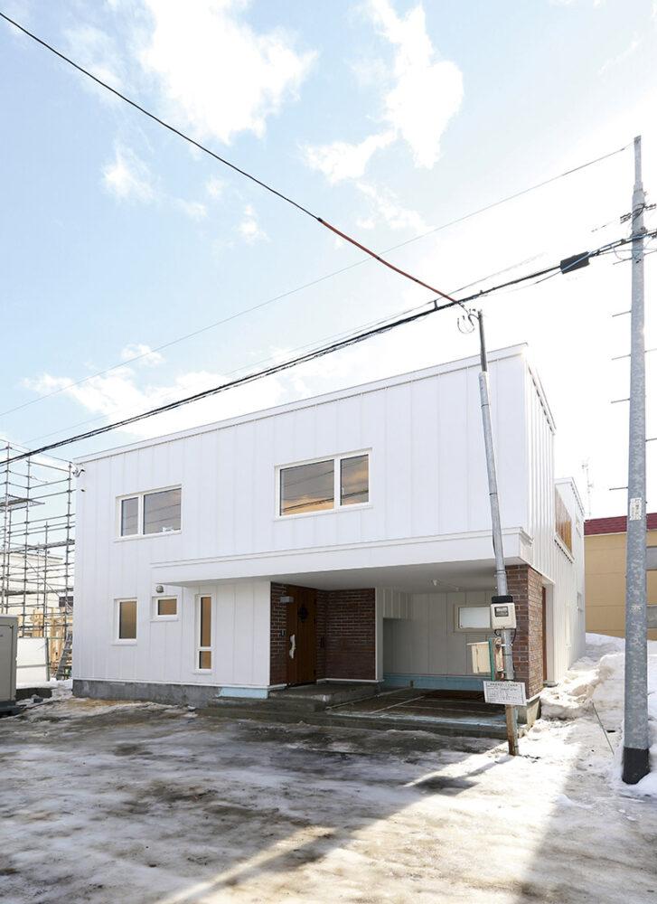 1階部分に江別レンガをあしらい白のガルバリウム鋼板で仕上げたシンプルデザインの外観