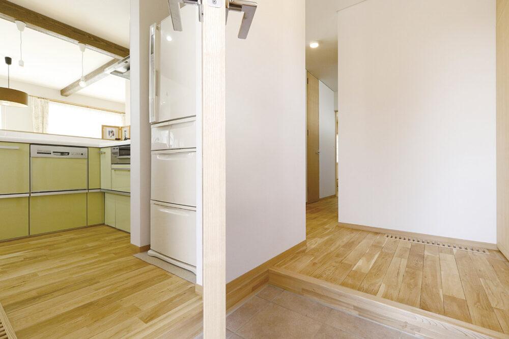 キッチンのトール型ドアを開けると玄関へ通じる。キッチンは食品庫や造作収納も備えた機能的なつくり