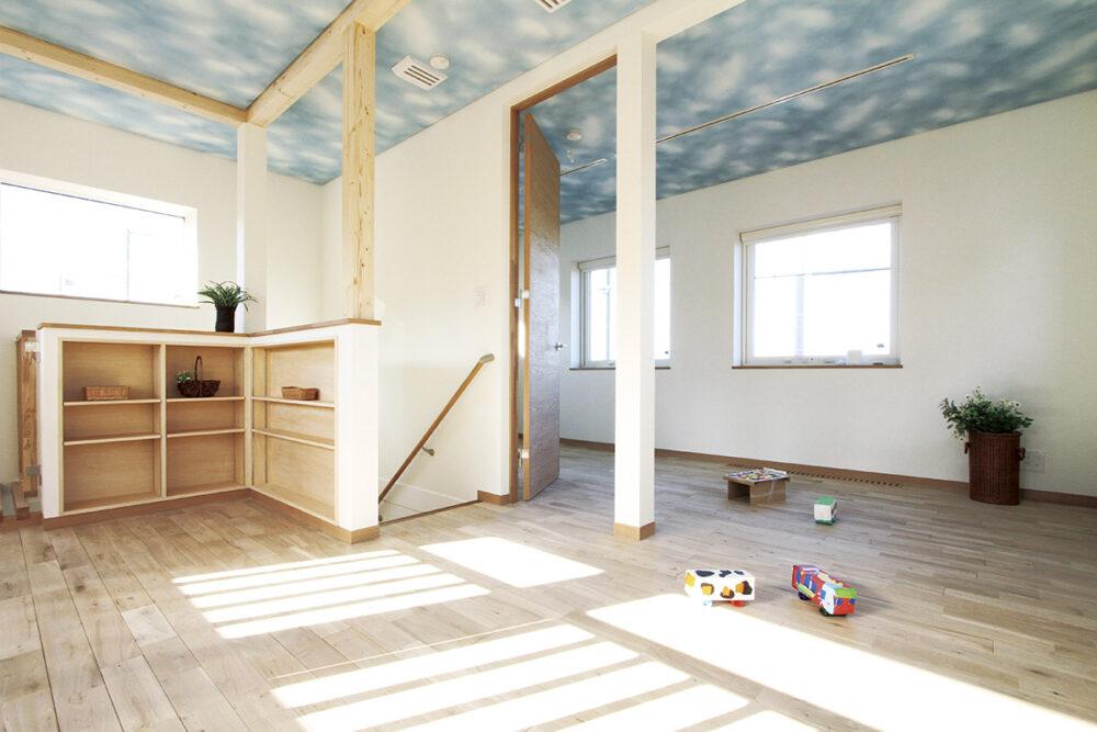 子ども部屋と吹き抜けに面したホール。青い空に白い雲が浮かぶ天井のクロスは子どもが自ら選んだ柄だそう