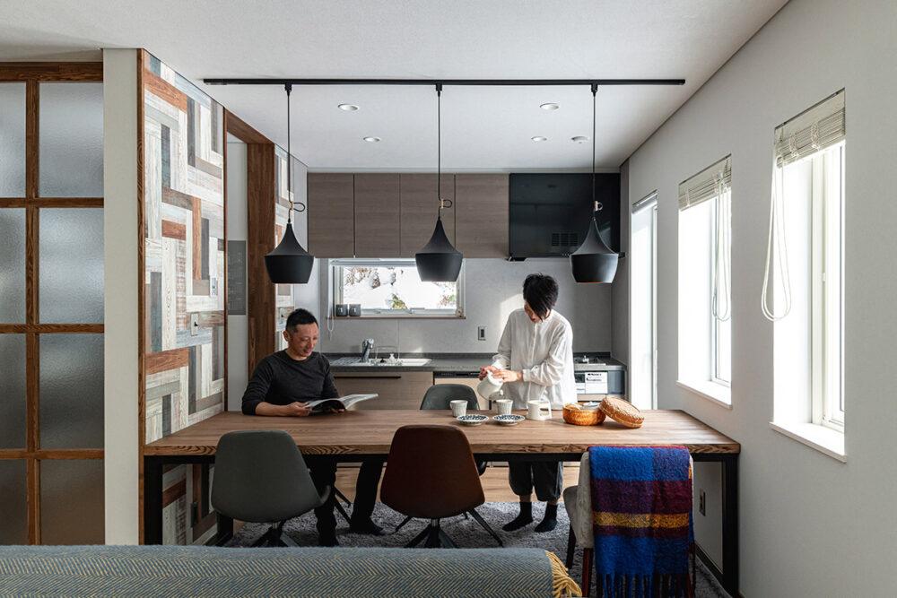 左右の壁にぴったりと収まる、作業台を兼ねた大きな造作のダイニングテーブル。磨りガラスの扉からまわりこんでキッチンにたどり着くというユニークな動線になっている