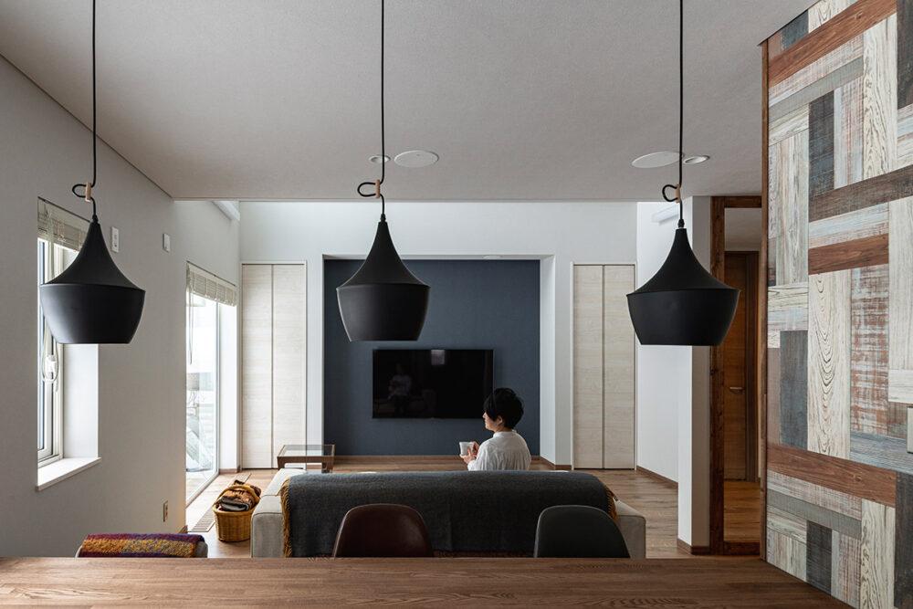 キッチンからリビングを見る。天井にはYさん希望のスピーカーが組み込まれている。「贅沢な音響システムで映画や音楽が楽しめます。最近は妻の方が満喫しているかも」