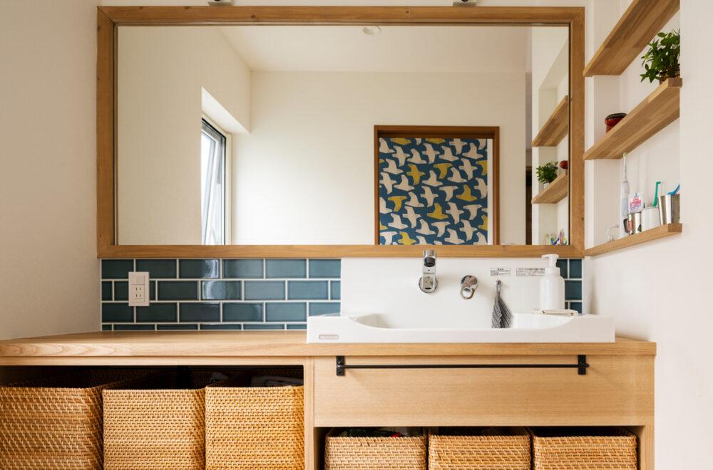 玄関から直結する造作洗面台。トイレの壁紙は扉を開けた際に鏡に映ることを想定して、青いタイルと色のトーンを合わせた