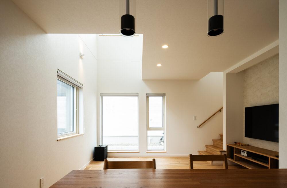 吹き抜けから優しい光が注ぐLDK。無垢床の質感も心地よい