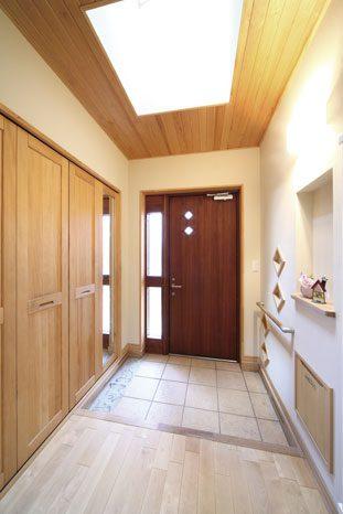 ホールから玄関を見たところ。土間床と大容量の造作下駄箱が設けられた開放的なエントランス空間