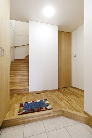 玄関土間には床暖房が設置され冬も暖かに家族を迎える。下駄箱とハイドアの建具はタモ無垢材を使用