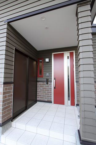 玄関まわりのデザインは、玄関ドアと小窓の枠の赤がアクセントに