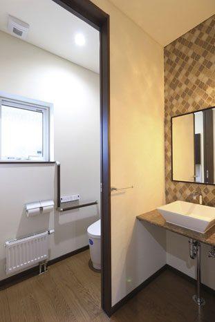 手すりも設置されたゆとりのあるトイレとデザインタイルが施された洗面スペース