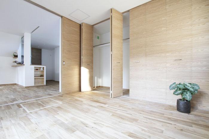 リビングとつながる寝室。高さ2.35mと広々と使える建具は木目が美しいタモ材で仕上げている