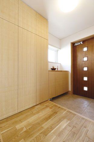 玄関まわりも素材のトーンを合わせて造作。天井まである収納も使い勝手とデザイン性を兼ね備えた設計