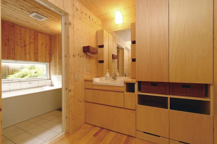 造作の洗面化粧台と造作の浴室。浴室の床はタイル、壁はカラマツ材、浴槽はホーローの仕上げ