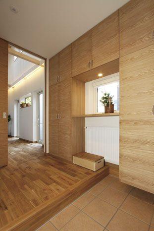 玄関の明かり取り窓を囲むように設けた大型の造作玄関収納。使い勝手の良い移動式ベンチも造作によるもの