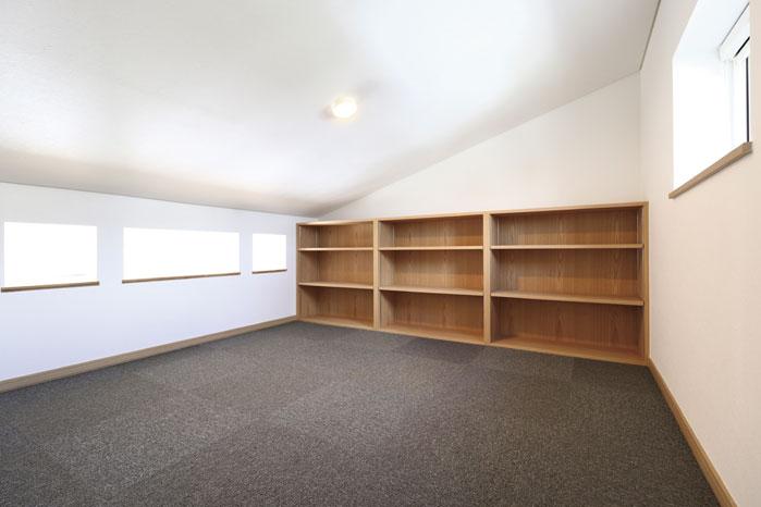 屋根なりの白い天井が明るさを増幅し採光も十分なロフト内部。造作による収納棚も