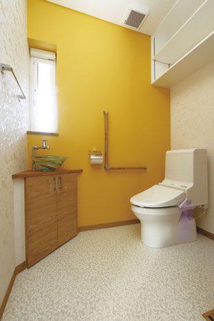 奥さんの希望が叶った、ガラス製の手洗いボウルや山吹色のクロスがおしゃれなトイレ