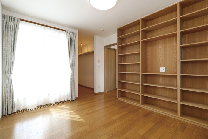主寝室には造作の幅広で高さもある収納棚を設置。写真奥はウォークインクローゼット